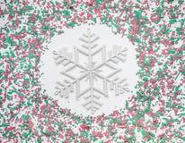 Confeti en color de la decoración de la Navidad con el copo de nieve en blanco Fotos de archivo libres de regalías