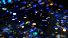 Confeti multicolor brillante Defocused del brillo, fondo negro Puntos ligeros del bokeh festivo abstracto del día de fiesta almacen de metraje de vídeo