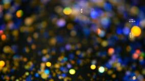 Confeti multicolor brillante Defocused del brillo, fondo negro Puntos ligeros del bokeh festivo abstracto del día de fiesta almacen de video