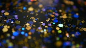 Confeti multicolor brillante Defocused del brillo, fondo negro Puntos ligeros del bokeh festivo abstracto del día de fiesta metrajes