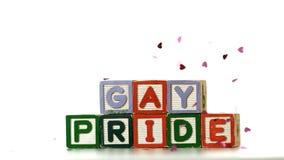 Confeti que cae en los bloques que deletrean orgullo gay almacen de metraje de vídeo