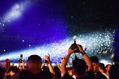 Confeti que lanza sobre la muchedumbre en el concierto vivo Imagen de archivo libre de regalías