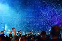 Confeti que lanza sobre la muchedumbre en el concierto vivo Foto de archivo libre de regalías