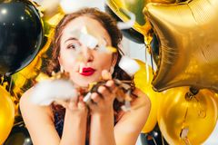 Confeti que sopla de la muchacha de los globos de la fiesta de cumpleaños imagenes de archivo