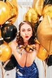 Confeti que sopla de la muchacha de los globos de la ocasión festiva imagen de archivo