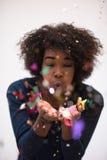 Confeti que sopla de la mujer afroamericana en el aire Imagen de archivo