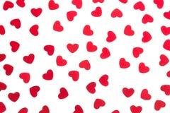 Confeti rojo de los corazones del modelo decorativo del día del ` s de la tarjeta del día de San Valentín aislado en el fondo bla Imagenes de archivo