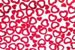 Confeti rojo de los corazones del modelo decorativo del día del ` s de la tarjeta del día de San Valentín aislado en el fondo bla foto de archivo libre de regalías
