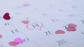 Confetis en forma de corazón que caen en un calendario en el 14 de febrero metrajes