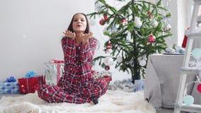Confetti счастливой девушки дуя деревом ель-рождества и окно в студии движение медленное 3840x2160 Принципиальная схема рождества сток-видео