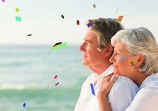 Confetti against elderly couple looking out to sea stock photo