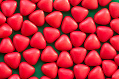 Confetti candies bon bons with the shape of a heart. Many red confetti candies bon bons with the shape of a heart royalty free stock photos