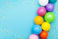 Confetti and colorful balloons for birthday party on blue table top view. Flat lay style.