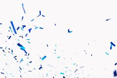 Confetti from crackers. Blue elements on a white background. Shot of confetti at a party. Festive mood. Serpentine, festive decor stock photo