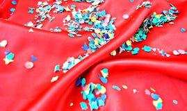 Confetti em um fundo vermelho Fotos de Stock Royalty Free