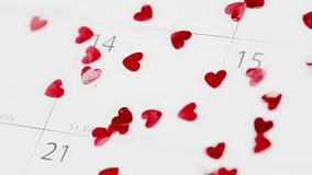Confetti falling on calendar showing Valentines day. Pink heart confetti falling on calendar showing Valentines day stock video footage