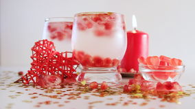 Confetti falling down, slow motion. Two glasses with alcohol decorated with candies, red candle, closeup. Romantic still life. Confetti and pomegranate seeds stock footage