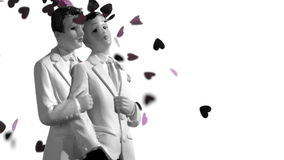 Confetti falling on gay groom cake toppers in black and white. In slow motion