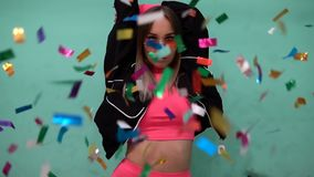 Confetti flies in front of a fashionable girl in pink clothes