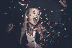 Confetti fun. Beautiful young woman throwing confetti and looking happy Stock Photo