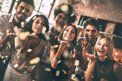 Confetti fun. Cheerful young people blowing confetti and smiling while enjoying party together Royalty Free Stock Photography