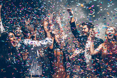 Confetti fun. Group of beautiful young people throwing colorful confetti while dancing and looking happy stock photo