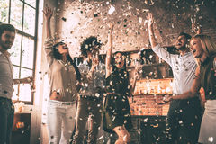 Confetti fun. Group of happy young people throwing confetti and jumping while enjoying home party on the kitchen Stock Photos