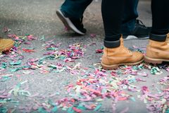 Confetti after a Chinese New Year parade in the City. Confetti on the ground after a Chinese New Year celebration in New York City in Chinatown. A pair of feet stock photography