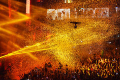Confetti over partying crowd during a live concert. CLUJ-NAPOCA, ROMANIA - AUGUST 7, 2016: Confetti cannons throwing confetti from the stage over the crowd at a royalty free stock image