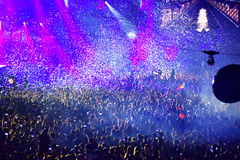 Confetti over partying crowd during a live concert. CLUJ-NAPOCA, ROMANIA - AUGUST 7, 2016: Confetti cannons throwing confetti from the stage over the crowd at a stock photography