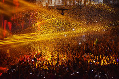 Confetti over partying crowd during a live concert. CLUJ-NAPOCA, ROMANIA - AUGUST 7, 2016: Confetti cannons throwing confetti from the stage over the crowd at a royalty free stock photography