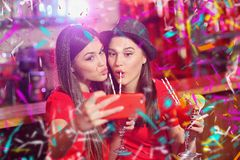 Confetti party. Two young girls lesbians at a party in the club take a selfie.  stock photography