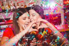Confetti party. Two young lesbian girls make a heart with their hands at a club party.  royalty free stock image