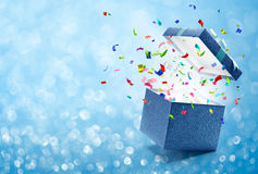 Confetti popping out from blue gift box. Bokeh background Stock Photo