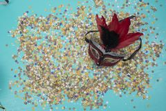 Confetti spread on blue background with a female carnival mask.  stock photos
