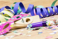 Confetti, streamers, mask and party blower on wood background stock photo