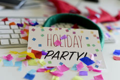 Confetti and text holiday party in an office. Closeup of an office desk full of confetti with a signboard with the text holiday party in the foreground and a stock image