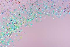 Confettien en fonkelingen op roze achtergrond royalty-vrije stock afbeeldingen