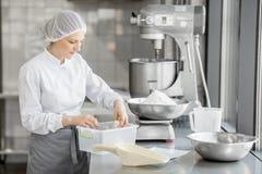 Confettiere della donna che lavora alla fabbricazione del forno immagine stock