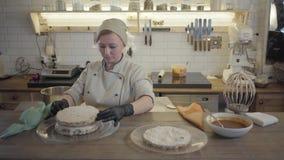Confettiere della donna che mette un secondo biscotto saporito sulla crema mentre facendo un dolce sui precedenti della cucina de archivi video