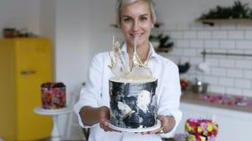 Confettiere femminile in camicia bianca che presenta dolce in bianco e nero decorato moderno nella sua cucina Frigorifero giallo  archivi video