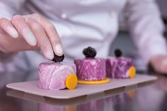 Confettiere professionista che dà classe matrice sulla decorazione dei dessert fotografie stock