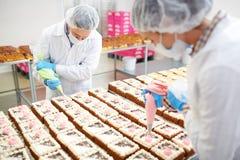 Confettieri che decorano i dolci con crema immagine stock libera da diritti