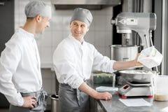 Confettieri che lavorano alla fabbricazione del forno immagini stock