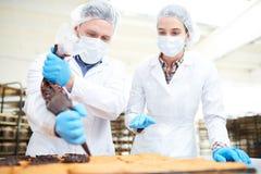Confettieri che versano la crema del cioccolato dalla borsa della pasticceria fotografie stock libere da diritti