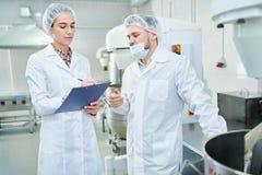Confettieri professionisti che discutono nella fabbrica fotografia stock libera da diritti