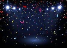 Confettis colorés sur le fond noir avec le projecteur Image libre de droits