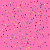 Confettis colorés sur le fond rose-clair Image libre de droits