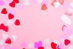 Confettis décoratifs de coeurs sur le fond rose Photographie stock libre de droits
