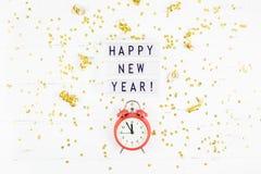 Confettis d'or de réveil de composition en nouvelle année image libre de droits